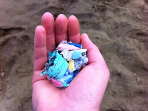 Handful of plastic debris from green sand beach